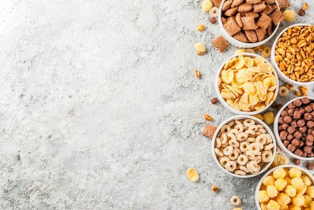 Insieme di vari cereali per la colazione, fiocchi di mais, sbuffi, pop, tavolo in pietra grigia copia spazio vista dall'alto