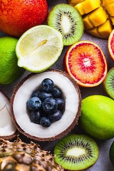Insieme di vari frutti arancia rossa, cocco, kivi, mango, ananas, lime, mirtillo