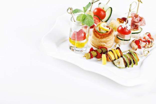 Insieme di vista del primo piano delle canape con le verdure, il salame, i frutti di mare, la carne e la decorazione sullo studio del piatto del whie isolato