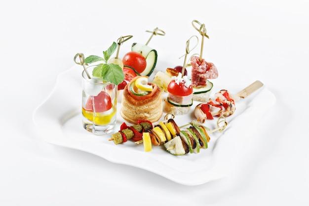 Insieme di vista del primo piano delle tartine con le verdure, il salame, i frutti di mare, la carne e la decorazione sul piatto bianco