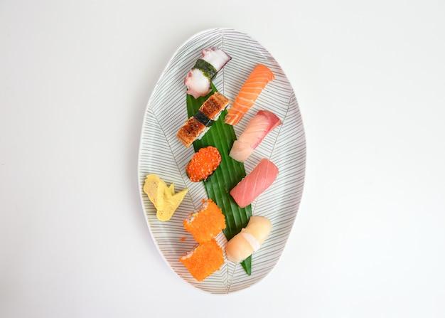 Insieme giapponese dei sushi di nigiri di alimento tradizionale sul piatto bianco
