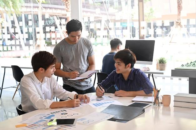 Insieme progetto di avvio con un gruppo di giovani uomo di brainstorming su carta e tablet.