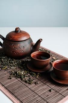 Insieme rustico di teiera e tazze con erbe