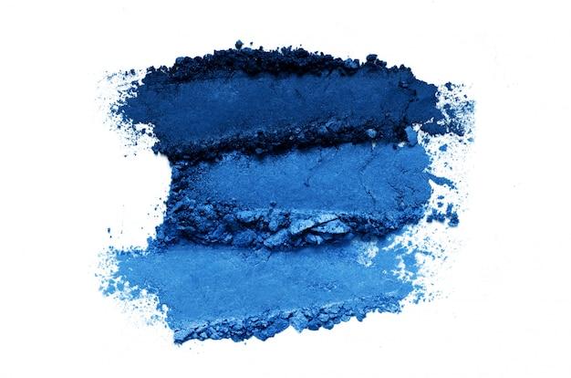 Insieme schiacciato di trucco dell'ombretto isolato su fondo bianco. colore dell'anno 2020 blu classico.