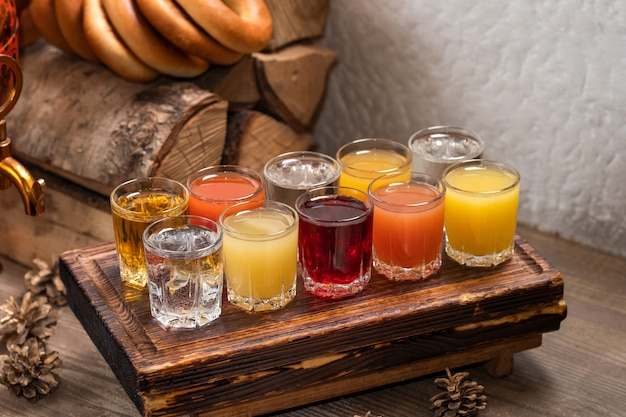Insieme variopinto dei cocktail alcolici in tiratori di bicchierini sulla tavola di legno per una festa alcolica.