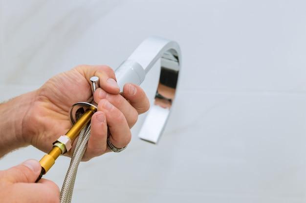 Installazione del rubinetto dell'acqua nell'idraulico del bagno al lavoro in bagno