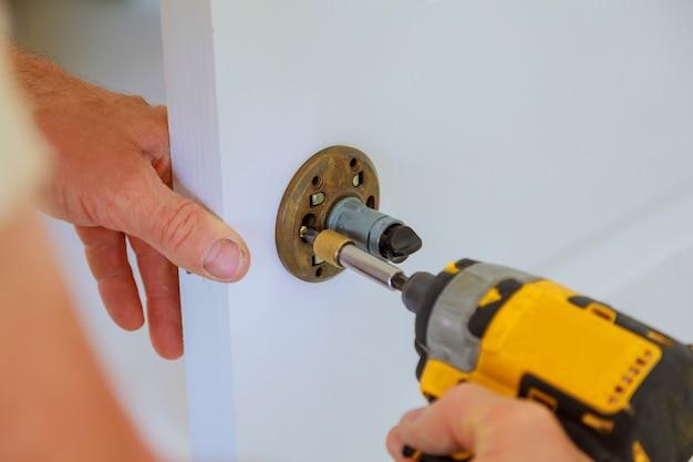 Installazione della serratura del carpentiere con trapano elettrico nella porta interna in legno