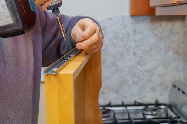 Installazione di mobili da cucina. assemblaggio del cassetto del ripiano