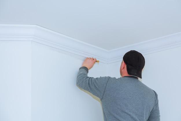 Installazione di modanature del soffitto. l'operaio fissa la modanatura del legno al soffitto