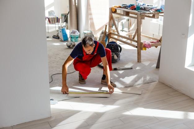 Installazione di piastrelle ceramiche per pavimenti - misurazione e taglio dei pezzi, primo piano