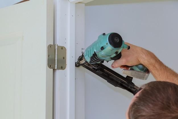 Installazione di una nuova porta interna, mano del carpentiere del primo piano che giudica sferica