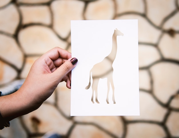 Intaglio della carta della giraffa della tenuta della mano