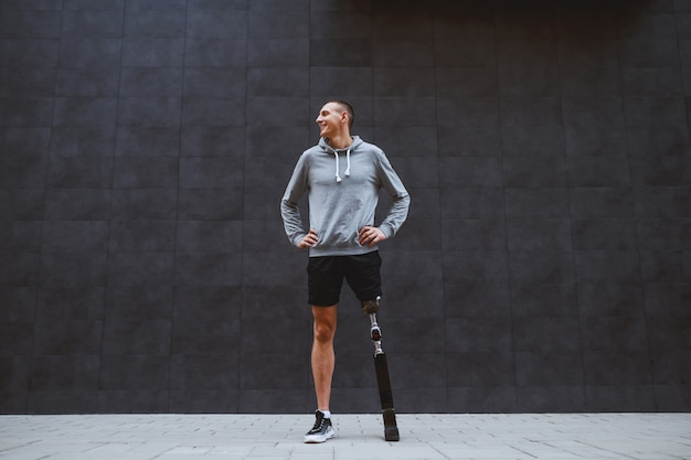 Integrale del giovane sportivo sorridente caucasico bello con la gamba artificiale in piedi con le mani sui fianchi davanti alla parete scura all'aperto.