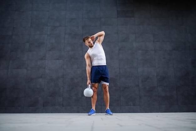 Integrale dell'uomo barbuto muscolare forte bello bello in pantaloncini corti e maglietta che posa con la campana del bollitore mentre stando all'aperto davanti alla parete grigia.
