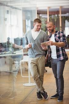 Integrale dell'uomo d'affari che mostra compressa digitale al collega