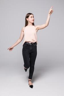 Integrale della giovane donna che indica il lato e che guarda là, isolato sulla parete bianca