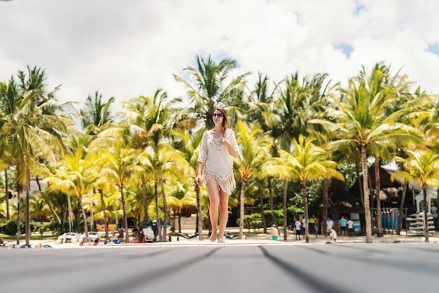 Integrale di bella bruna che cammina sulla strada in abito estivo e con occhiali da sole.