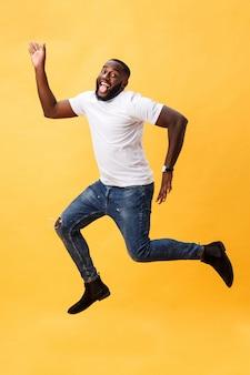 Integrale di giovane uomo di colore bello che salta contro il fondo giallo.
