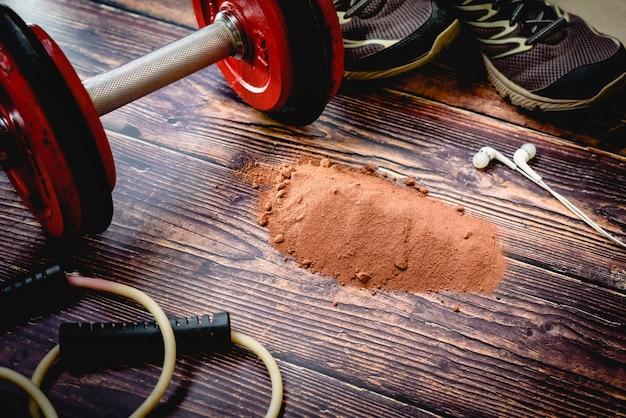 Integratore di siero di latte proteico al cacao in polvere sul pavimento di una palestra durante un allenamento.