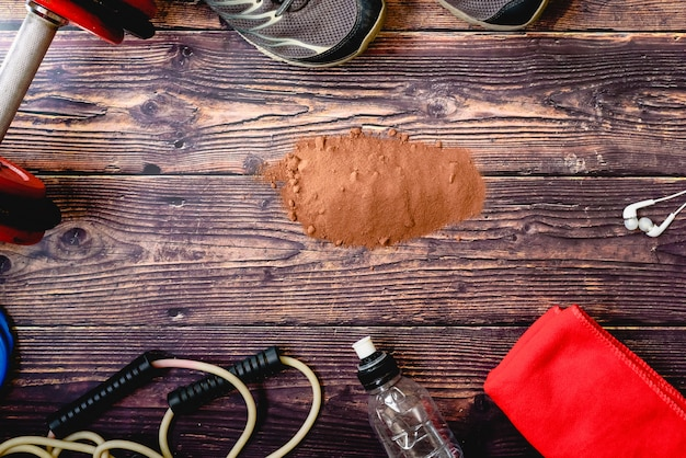 Integratore sportivo a base di siero di latte, proteine e carboidrati con aroma di cacao, sfondo con accessori fitness