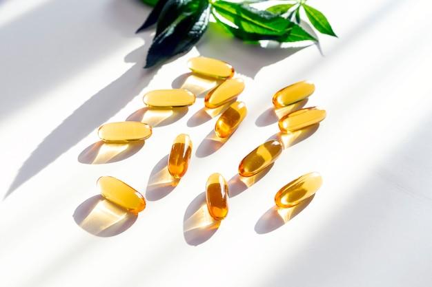 Integratori alimentari a base di erbe e vitamine d, a o e decorate con foglie verdi