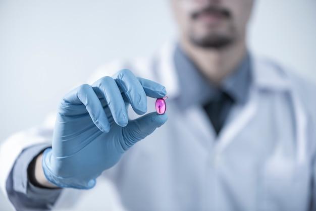 Integratori alimentari olio di fegato di merluzzo omega-3 vitamina d, capsule di olio di pesce, capsula di olio in mano di ricercatore