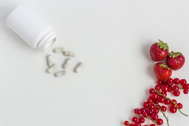 Integratori vitaminici in capsule con bacche fresche dal barattolo di medicinali.
