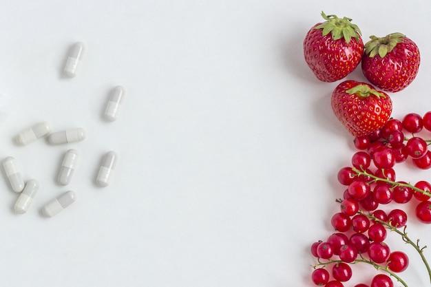 Integratori vitaminici in capsule con bacche fresche.