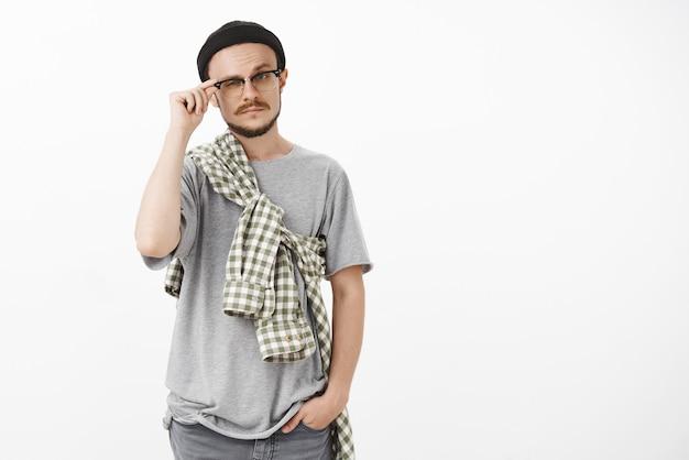 Intelligente bel maschio artistico con barba e baffi alzando le sopracciglia e strizzando gli occhi toccando il bordo degli occhiali in piedi curioso e incuriosito in berretto e occhiali