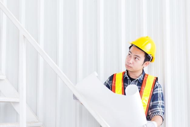 Intelligente ingegnere civile indossare il casco di sicurezza e tenere la costruzione a