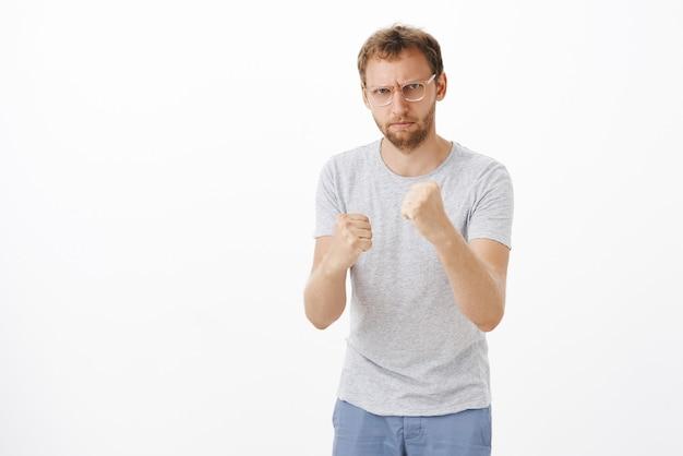 Intenso maschio arrabbiato dall'aspetto serio con setole negli occhiali che aggrotta le sopracciglia alzando i pugni per difendersi dagli attacchi