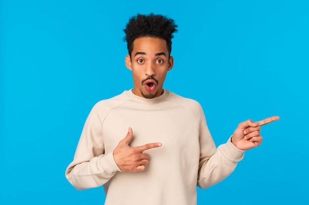 Interessante modello afroamericano giovane interrogato e impressionato con baffi, taglio di capelli afro, curioso dell'evento nelle vicinanze, puntando le dita a destra, bocca aperta senza fiato divertito, aspetto meravigliato