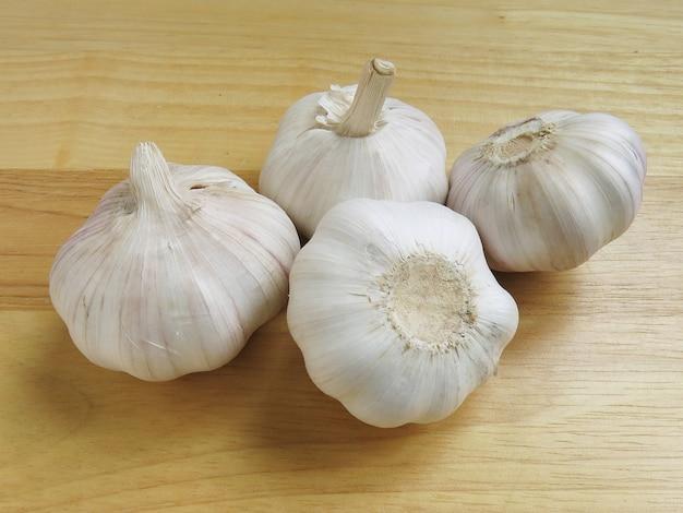 Interi chiodi di garofano aglio su fondo in legno