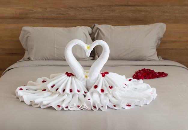 Interior design camera da letto con cigni dalla decorazione asciugamano sul letto