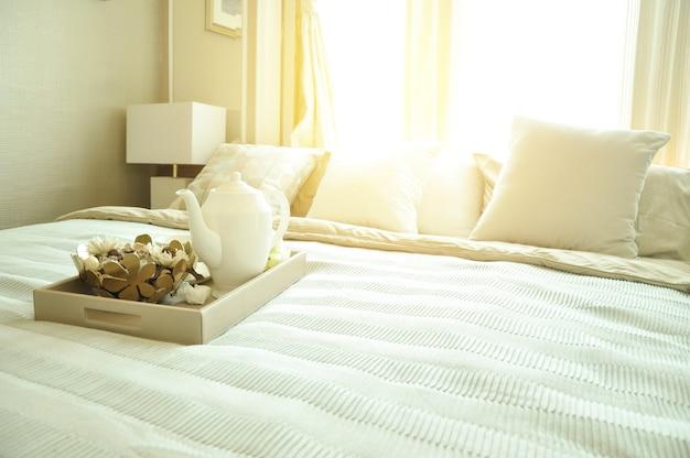 Interior design camera da letto con cuscini bianchi di lusso sul letto e lampada da tavolo decorativa.