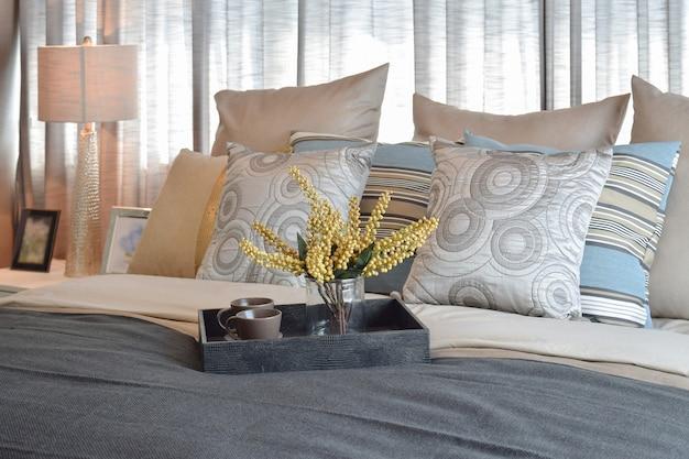 Interior design camera da letto di lusso con cuscini a righe e set da tè decorativo sul letto