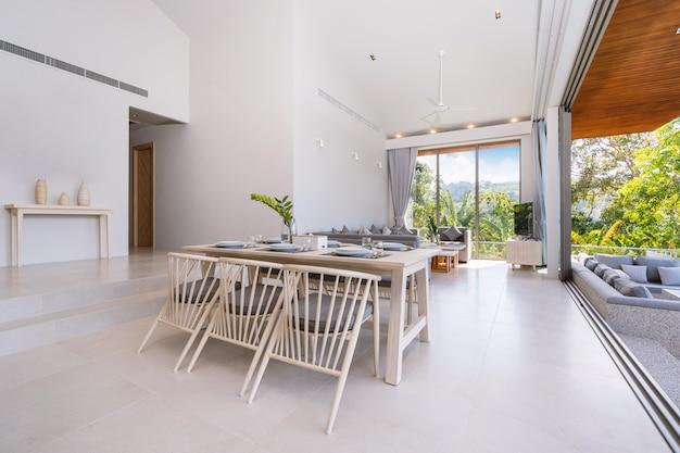 Interior design in piscina villa, casa e casa dispongono di tavolo da pranzo e sedia da pranzo nella sala da pranzo con vista sulla piscina