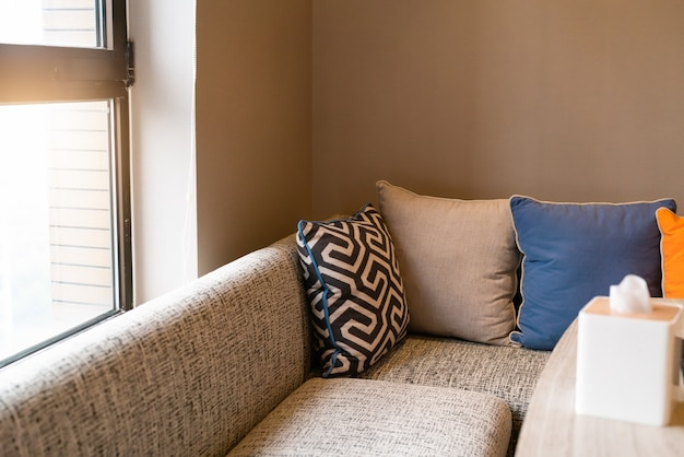 Interior design per la casa, divano accogliente in soggiorno con cuscino colorato.