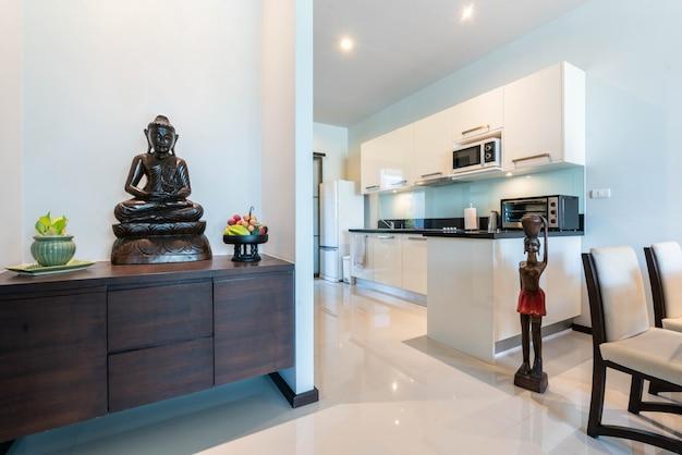 Interior design villa completamente arredata dotata di cucina, tavolo da pranzo e decorazione buddha