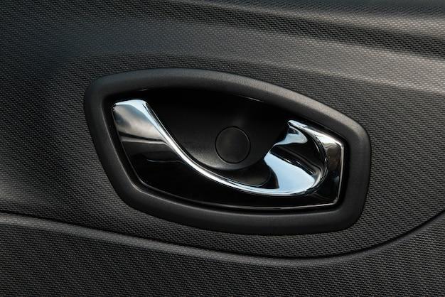 Interiore dell'automobile con il primo piano della maniglia interna della porta