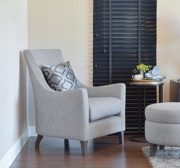 Interiore moderno del salone con il cuscino sulla poltrona grigia a casa