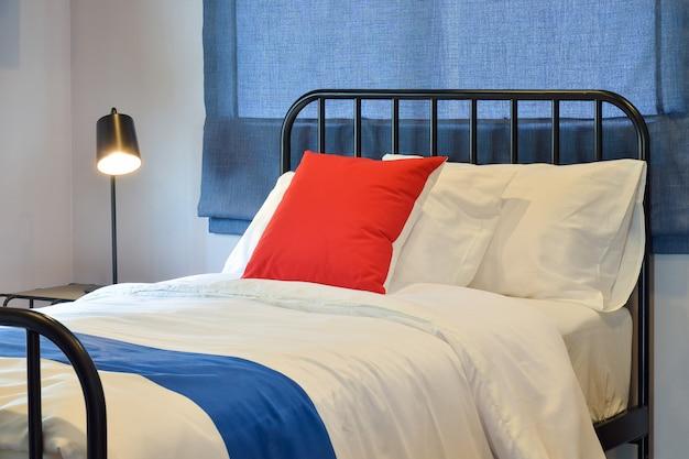 Interiore moderno della camera da letto con i cuscini e ciechi romani blu