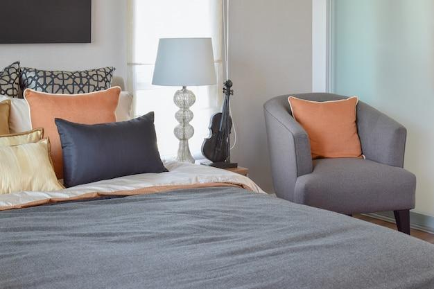 Interiore moderno della camera da letto con il cuscino arancione sulla lampada grigia del comodino e della sedia a casa