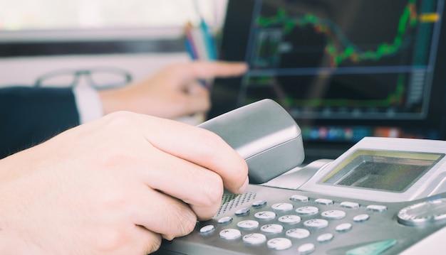 Intermediario che fa una telefonata a un operatore di borsa per fare piani per la compravendita di azioni mentre lo stock sale.