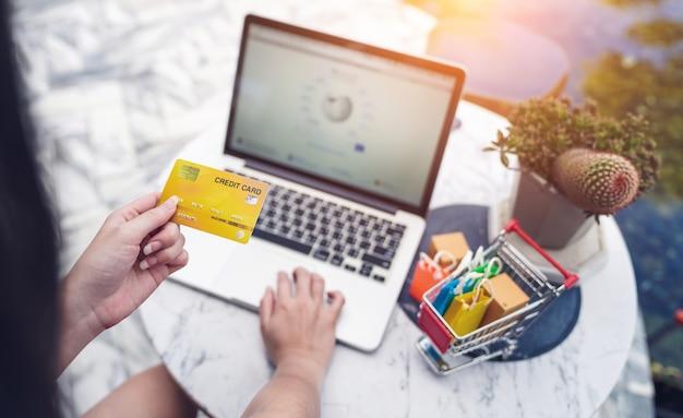 Internet banking e concetti di shopping online, mani di donna in possesso di carta di credito per il trasferimento di denaro