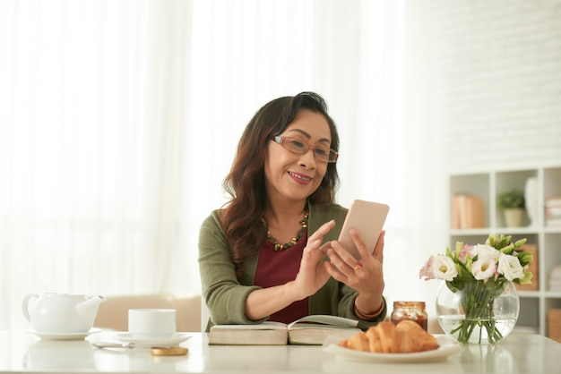 Internet praticante il surfing della donna asiatica adulta facendo uso del suo smartphone che si siede alla tavola a casa