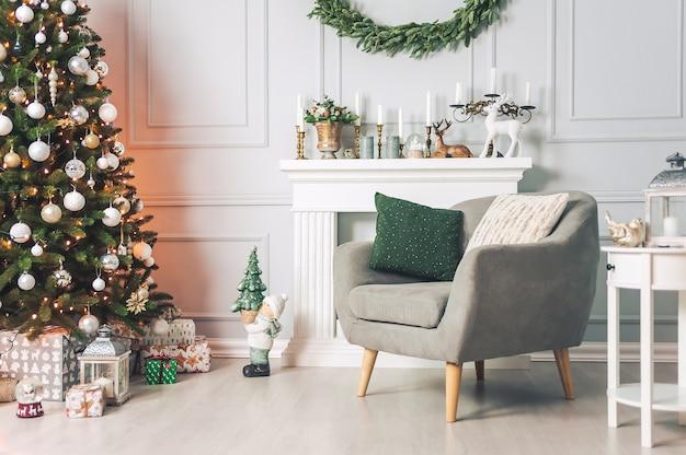 Interni classici con tavoli di una poltrona e un albero di natale con decorazioni su uno sfondo chiaro di un muro con camino.