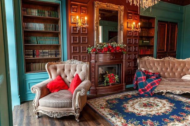 Interni classici di lusso della biblioteca di casa. salotto con libreria, libri, poltrona, divano e camino.