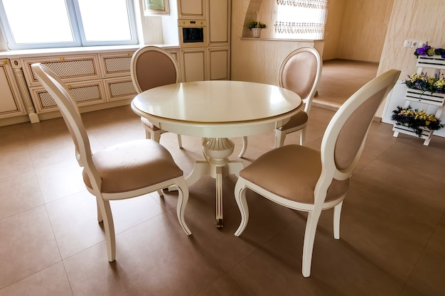 Interni di lusso arredati moderni. cucina in casa di lusso con mobili beige. tavolo e sedie