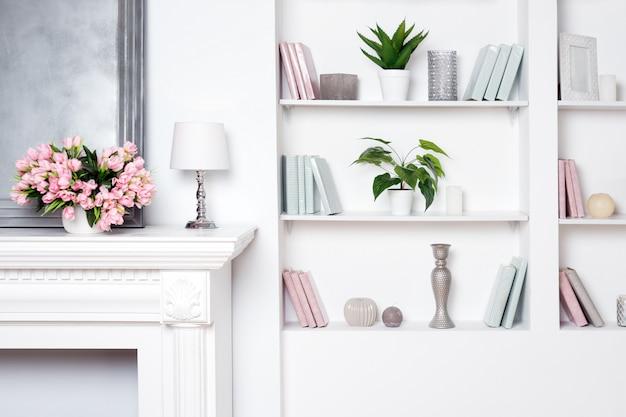 Interni di lusso chiaro con camino e fiori. scaffali con libri e decorazioni